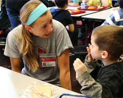 Zillmer visits with a student at Thomas Metcalf School student during lunch.