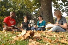 Students study on the Quad under a tree