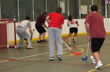 Students play floor hockey