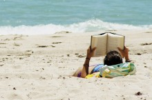 Woman reads on a beach