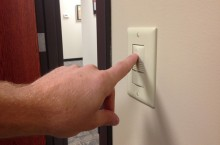 Fingers pushes a light switch