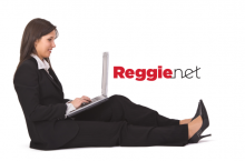 Woman in business suit using a laptop and the ReggieNet logo.