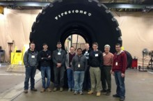 Engineering technology students in front of a 15,000-pound tire