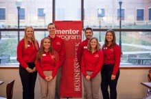 A group of students standing next to mentor program sign
