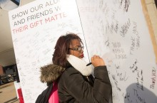Photo of student signing Giving Tuesday thank you card.