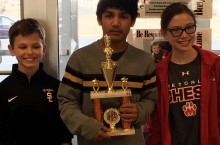 students pose with their fourth place Junior High division chess trophy.