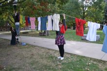 Illinois State student and ISU F.L.A.M.E. member Kristina Harlow helps hoist The Clothesline.