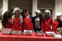 Dean of Students Office staff members serve breakfast to students during the Late Night Breakfast.