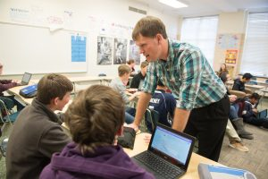 Alum and current graduate student Andy Goveia '13 works with his students at Thomas Metcalf.