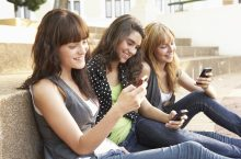 image of Group Of Teenage Students Sitting Outside On College Steps Using Mobile Phone