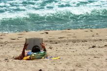 Woman reads on the beach