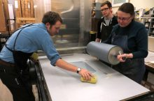 Artists work on a print