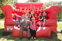 Dietz poses with students on giant red chair