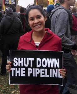 "Cecilia holding ""shut down the pipeline"" sign"