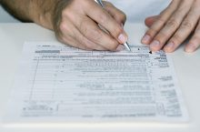 Man Filling out Tax Form --- Image by © Royalty-Free/Corbis
