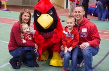 Family of four with Reggie Redbird