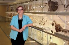 Deborah Hull-Walski stands at one of the exhibits inside Q?rius.