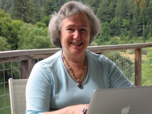 Joan Lippincott sitting on deck in front of laptop