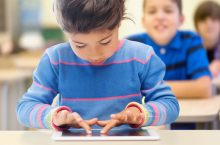 image of a little girl in a classroom, working on an iPad.