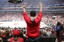 Man standing and cheering at basketball game