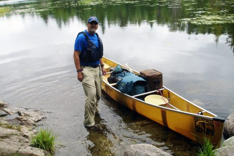 man standing next to canoe