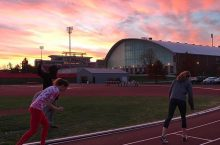Two sprinters preparing to run on the track with a sunset over Horton Fieldhouse in the background