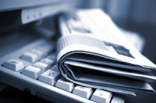 image of Newspapers on the computer keyboard close up