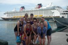 Students pose near a cruise liner