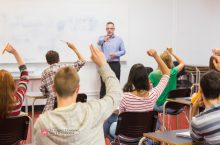 Teacher in front of class, student with raised hands