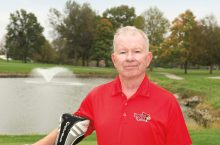 Professor Emeritus Robert Bradley on golf course with clubs