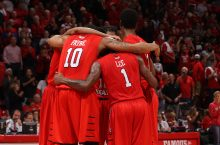 Men's basketball players huddling on the court