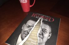 Redbird Scholar magazine on a table next to a coffee mug