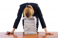 Instructor with head on stack of papers