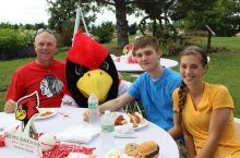 Family of three sitting at table with Reggie Redbird