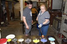 An alumna picks out colors for a glass paperweight with Tyler Wolf, a senior art major, at an alumni event.