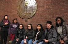 High schoolers pose under ISU seal