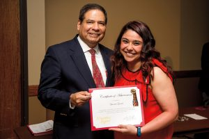 Jaime Flores '80 helped create Nuestros Logros. He presented an award to Yesenia Garcia, M.S. '16.