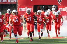 Redbird football players running onto the field