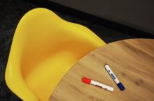 Two markers on a table next to a chair