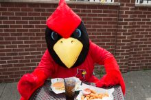 Reggie Redbird with burger and pop
