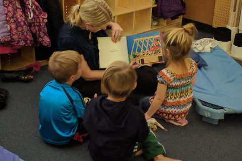 Woman reading to three children