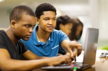 Students looking at laptop with photo with logo