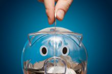 hand slipping a coin into a plastic piggy bank