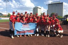 Illinois State softball team on field near Tri-Towers