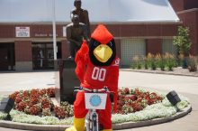 Reggie Redbird rides a bike from the Town of Normal's rental program, Bike Share 309.