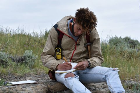 Young man making notes while sitting on a grassy ridge