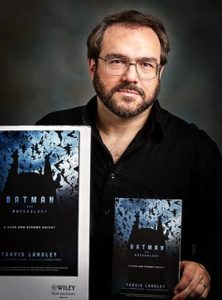 Travis Langley holding his book on the psychology of Batman
