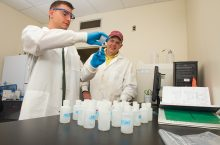 two men in lab coats, one pouring a substance into a beaker