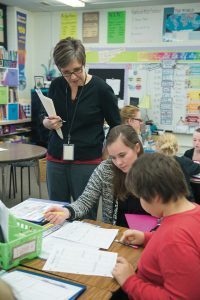 Deborah MacPhee (standing) developed an embedded course where Professional Development School interns, classroom teachers, and administrators explore literacy practices together.