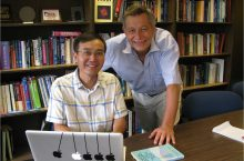Professors Q. Charles Su and Rainer Grobe work at a laptop in front of rows of books